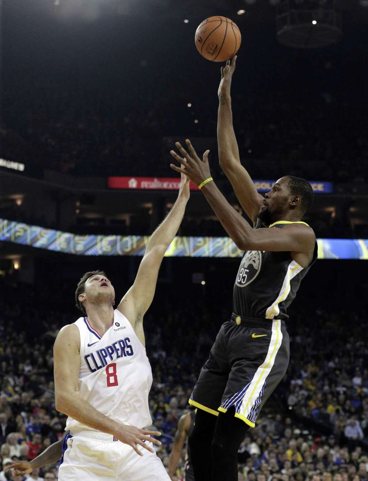 Kevin Durant (35) shoots over Danilo Gallinari (8) in the first half as the Golden State Warriors played the Los Angeles Clippers at Oracle Arena in Oakland, Calif., on Sunday, December 23, 2018.