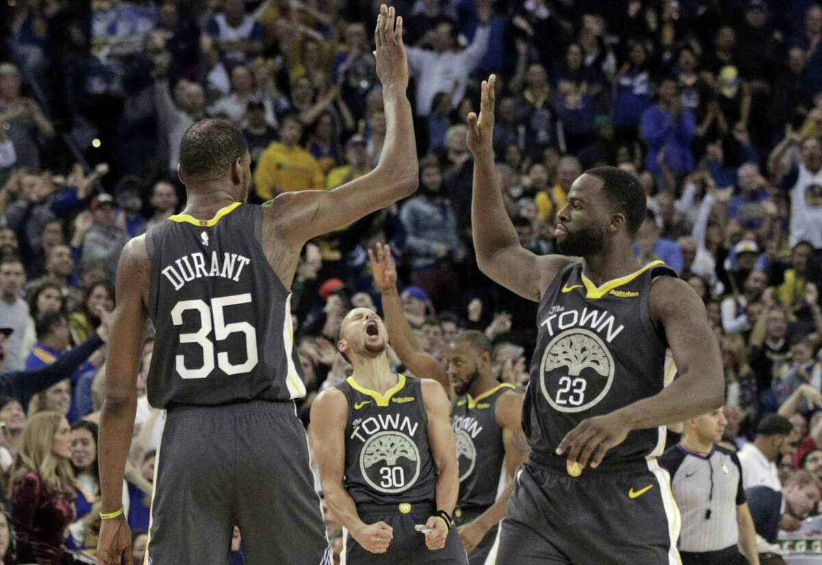 The Warriors celebrate a three point shot by Kevin Durant (35) to put the Warriors ahead in the second half as the Golden State Warriors played the Los Angeles Clippers at Oracle Arena in Oakland, Calif., on Sunday, December 23, 2018.