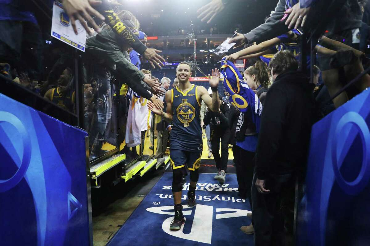 A fan grabs Golden State Warriors' Stephen Curry leaves the floor following the Warriors' 110-93 win over Memphis Grizzlies during NBA game at Oracle Arena in Oakland, Calif. on Monday, December 17, 2018.