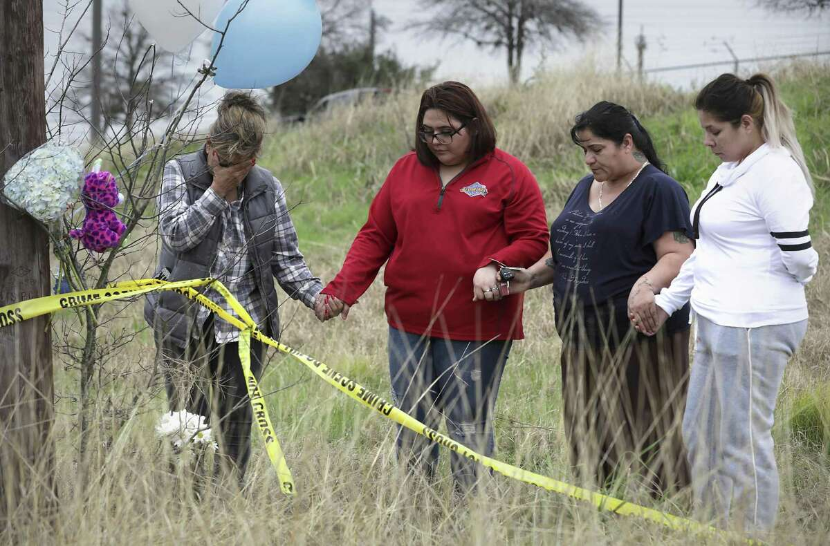 Mourners Sylvia Santana, left to right, Diamond Moreno, Margarita Santoya and Mary De La Rosa pray on Jan. 11, 2019, after placing flowers, balloons and stuffed toys near where the body of 8-month-old King Jay Davila was found. His body was wrapped in a blanket, placed inside a backpack and buried next to Rosillo Creek by Rittiman Road.