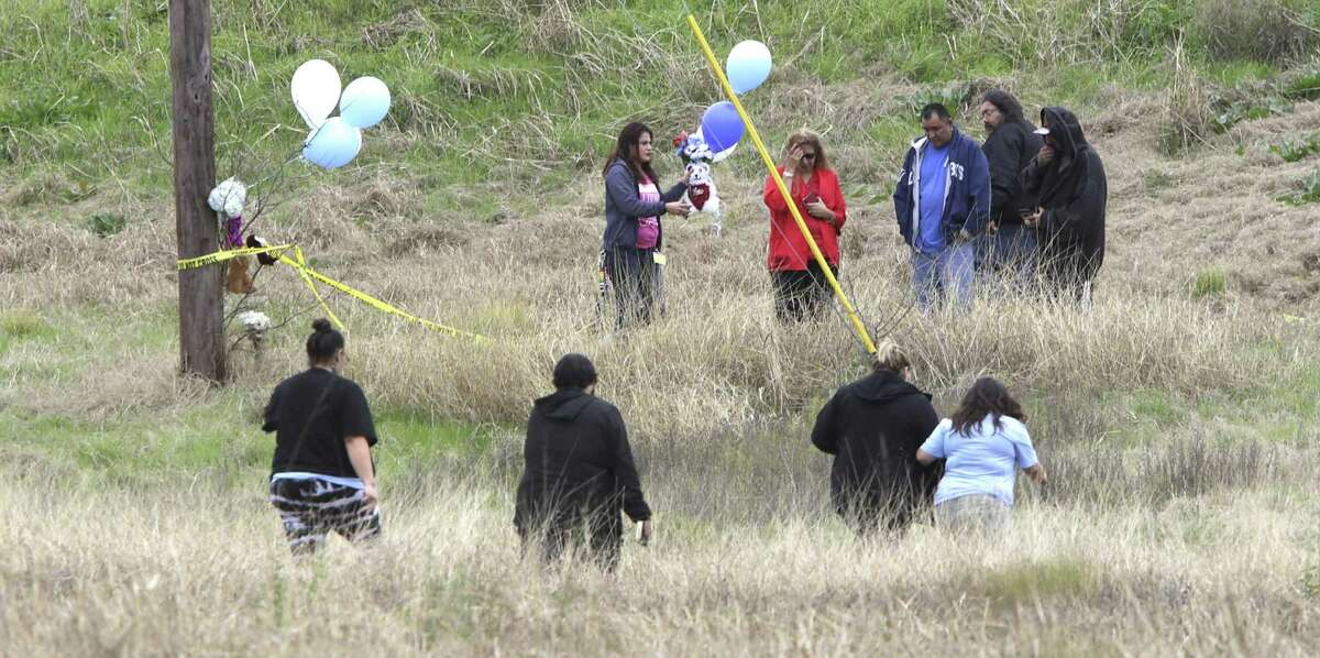 Mourners walk to an empty field to place flowers, balloons and stuffed toys on Jan. 11, 2019, near where authorities found the body of 8-month-old King Jay Davila wrapped in a blanket and buried in a backpack next to Rosillo Creek by Rittiman Road. His father reported him kidnapped a week before, a story to cover up his death.