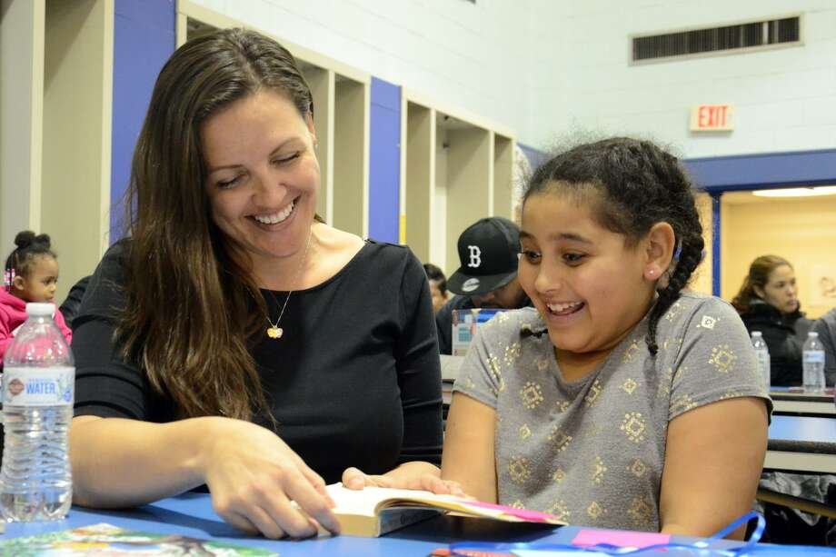 Heather Gilbertie reads a book with her daughter Sophia Freeman at Jefferson Elementary School on Thursday night. Photo: Tatiana Flowers / Hearst Connecticut Media / Norwalk Hour