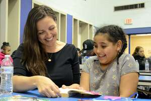 Heather Gilbertie reads a book with her daughter Sophia Freeman at Jefferson Elementary School on Thursday night.