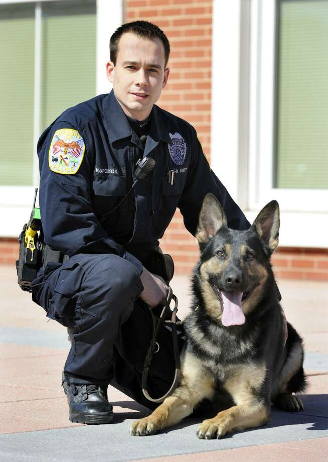 File photo of Danbury Police Officer Travis Kupchok crouches with Koda, his canine partner, Tuesday, March 6, 2012. Photo: Carol Kaliff / Carol Kaliff / The News-Times