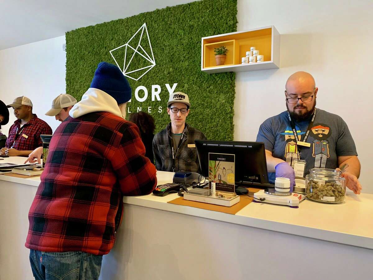 The first recreational marijuana customer in Great Barrington, Mass., approaches the sales counter at Theory Wellness on Friday, Jan. 11, 2019.