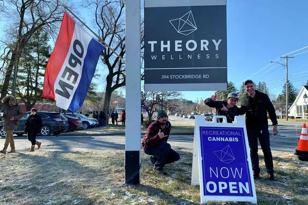 """A cheer rang out from the line as Theory Wellness marijuana store staff brought the """"Now Open"""" sign to the roadside in Great Barrington, Mass., on Friday, Jan. 11, 2019."""