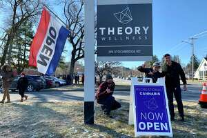 "A cheer rang out from the line as Theory Wellness marijuana store staff brought the ""Now Open"" sign to the roadside in Great Barrington, Mass., on Friday, Jan. 11, 2019."