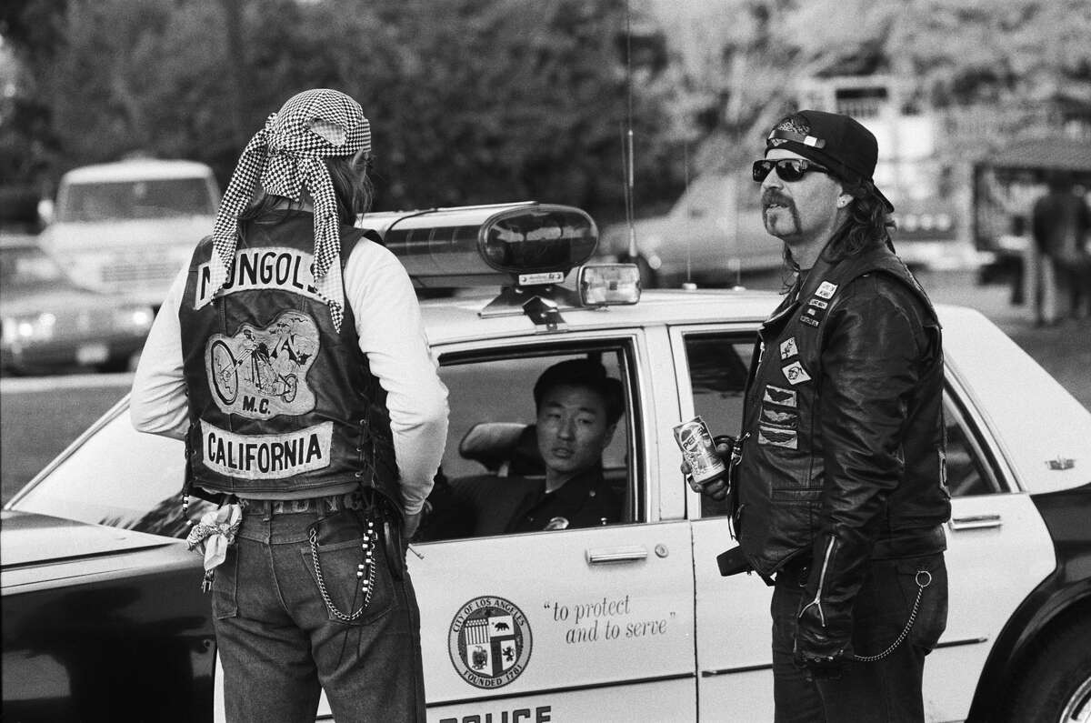 Members of the Long Beach chapter of the Mongols motorcycle club chat with a police officer at a picnic in a park in January 1991 in San Pedro, California.