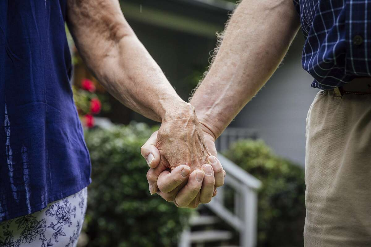 FILE -- Glenn and LouJean Nelson hold hands in Tallahassee, Fla., May 26, 2018. There are steps retirees can take to lengthen the life of their savings, such as mindful spending, when markets are less than cooperative. (Audra Melton/The New York Times)