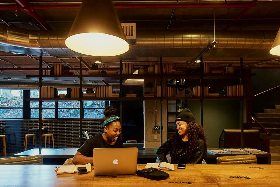 Heather White (left) and Melisa Valdez of Trillfit, a boutique fitness studio, work at the Revolution Hotels co-working space in Boston. Photo: Tony Luong / New York Times 2018