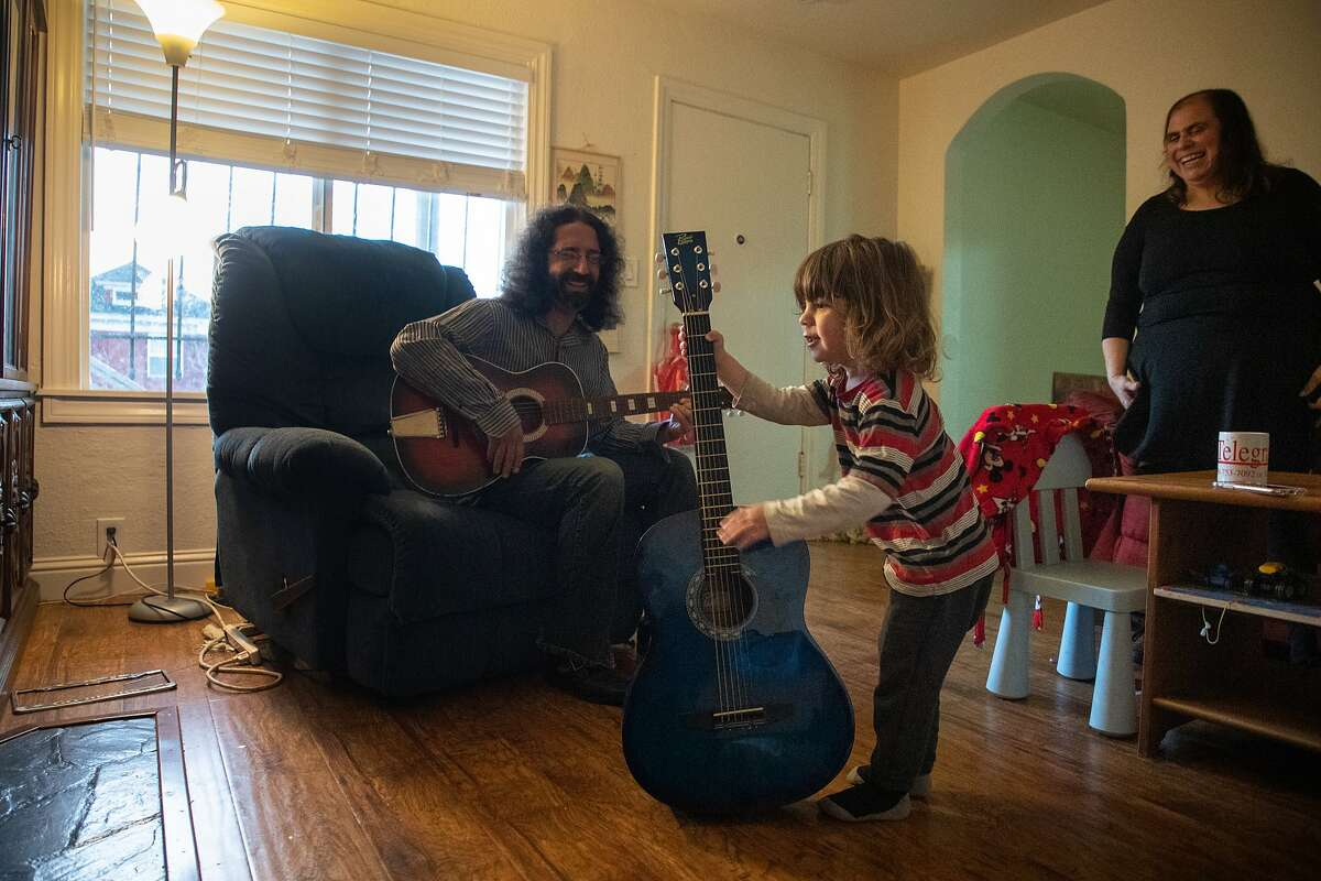 Adam Sandler plays guitar with son Baz, 3, on Friday, Jan. 11, 2019, in Berkeley, Calif. Mother Allision Landa watches in the background. They recently moved into this 2-bedroom duplex a mile from their former home of 13-years.
