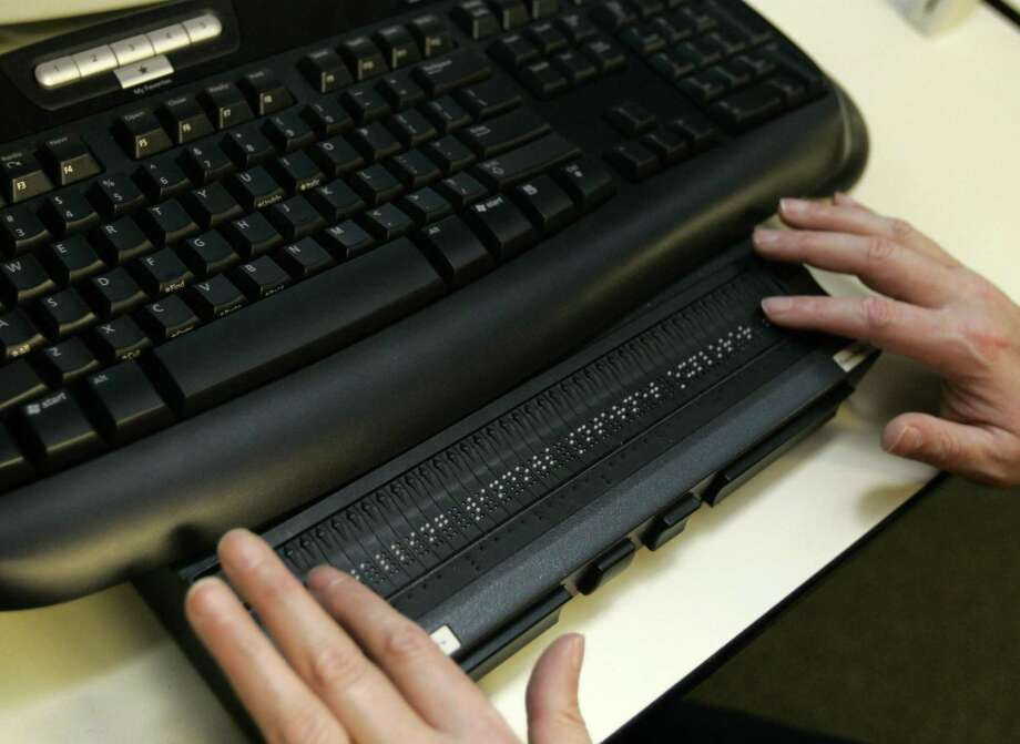 """A Microsoft Corp. employee moves his fingers over a """"braille display"""" in 2006 in Redmond, Wash. There is a shortage of IT workers, a problem that apprenticeships could help solve. Photo: TED S. WARREN /AP / AP"""