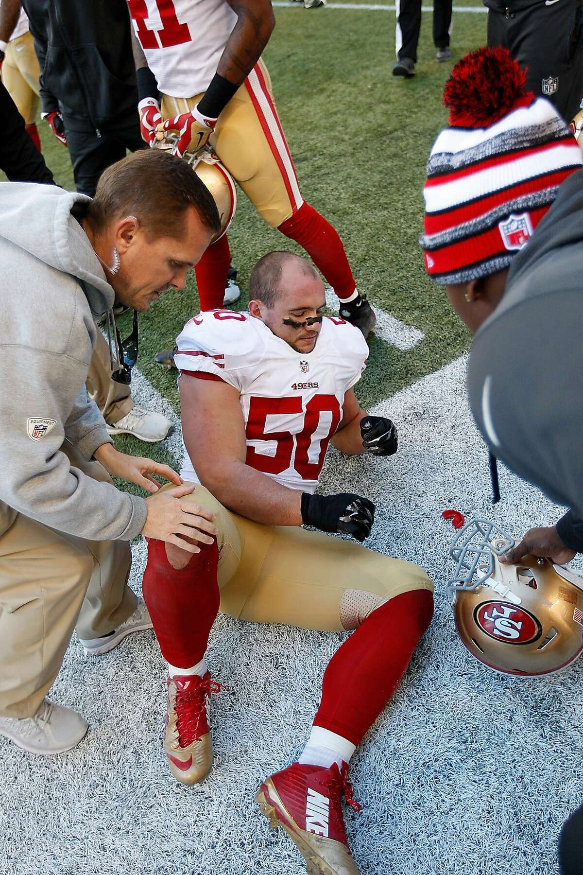Director of Football Operations and Sports Medicine Jeff Ferguson of the San Francisco 49ers checks on Chris Borland #50 ankle during the game against the Seattle Seahawks at CenturyLink Field on December 14, 2014 in Seattle.