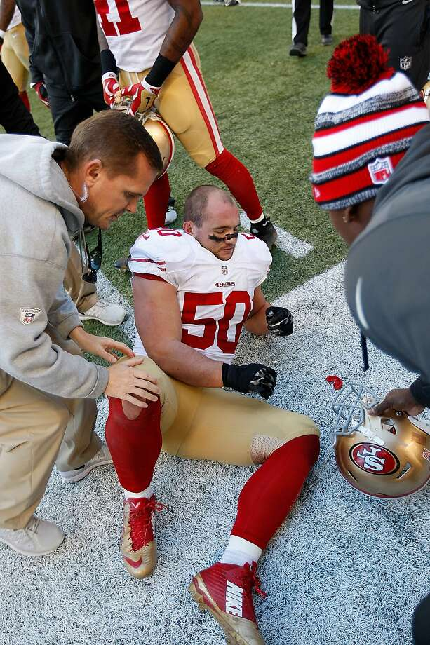 Director of Football Operations and Sports Medicine Jeff Ferguson of the San Francisco 49ers checks on Chris Borland #50 ankle during the game against the Seattle Seahawks at CenturyLink Field on December 14, 2014 in Seattle. Photo: Michael Zagaris / Getty Images