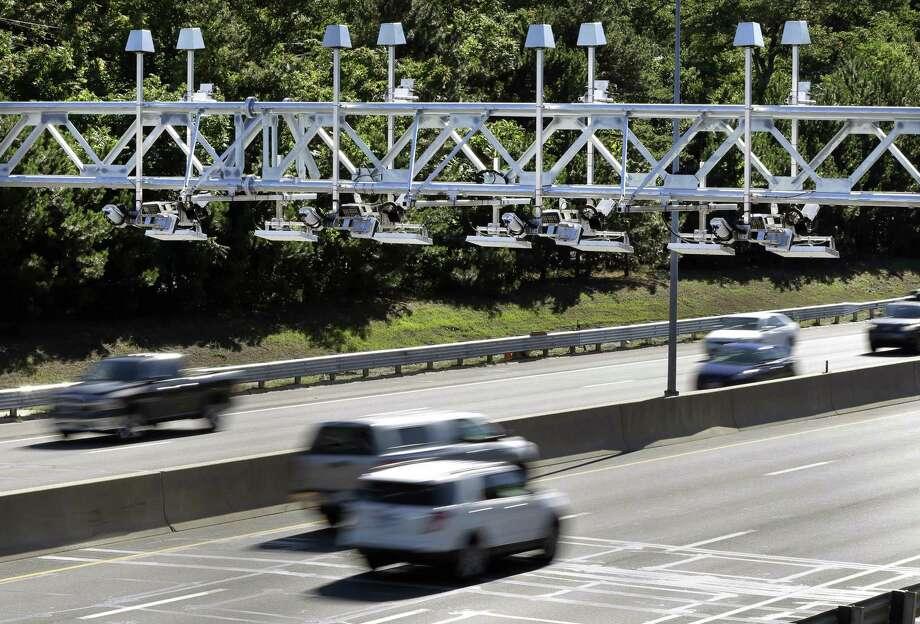 Cars pass under toll sensor gantries hanging over the Massachusetts Turnpike in Newton, Mass. Photo: Associated Press / AP