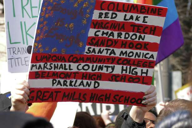 A poster depicts the U.S. flag with school names, all of which suffered losses of students killed by gun violence, during the March For Our Lives rally to demand stricter gun control laws on Saturday, March 24, 2018, in Washington, D.C. A reader says the crisis America should focus on is gun violence, not what's happening at the border.