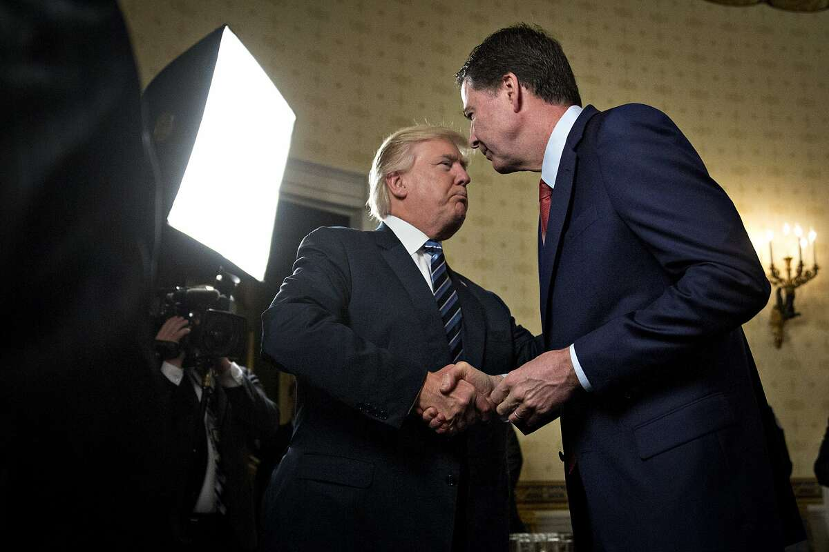 WASHINGTON, DC - JANUARY 22: U.S. President Donald Trump, left, shakes hands with James Comey, director of the Federal Bureau of Investigation (FBI), during an Inaugural Law Enforcement Officers and First Responders Reception in the Blue Room of the White House on January 22, 2017 in Washington, D.C. Trump on June 16 lashed out at the Justice Department official with authority over the special counsel probe of Russian election-meddling, and acknowledged that his firing of Comey as FBI director is a focus of the investigation. Photo by Andrew Harrer-Pool/Getty Images)