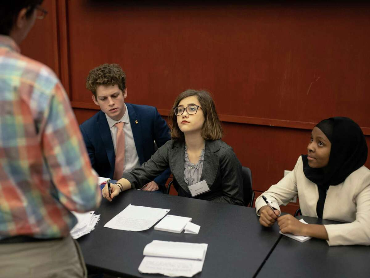 """Members of the Human Rights Council - from left, Henry Livingstone, Alison Fowler, and Fartun Yussuf - speak with a delegate during the Model United Nations San Antonio held on Trinity University's campus on Friday, Jan. 11, 2019. The conference lasted two days and included 1,200 students from 35 schools from San Antonio, Austin, Houston, Dallas and Monterey Mexico. Students who participated as delegates representing the world's countries debated topics such as """"Combating Issues Elicited by the Illegal Sex Trade,"""" and """"Limiting the Use of Armed Drones in War Zones."""""""