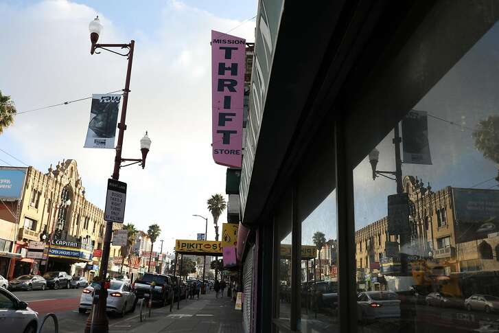 Signage for the closed Mission Thrift store stands above Mission Street as the El Capitan Theater is seen across from it and reflected in a store window on Mission Street on Thursday, January 10,  2019  in San Francisco, Calif.