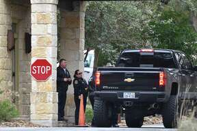Security officers and Bexar County sheriff's officials check vehicles going into the gated Anaqua Springs Ranch community near Leon Springs after three people were found shot to death in an upscale home there Thursday.
