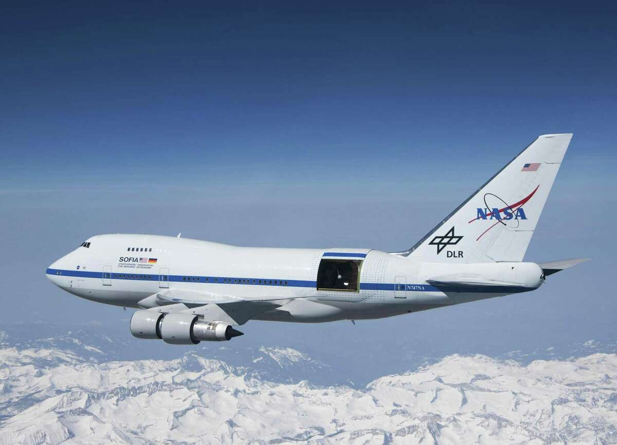 """This undated photo provided by NASA shows SOFIA over the snow-covered Sierra Nevada mountains with its telescope door open during a test flight. The world's largest airborne observatory was supposed to be parked in Seattle this week, so thousands of scientists attending the """"Super Bowl of Astronomy"""" could behold this marvel: a Boeing 747, like this one shown, for example, outfitted with a massive telescope used to study the fundamental mysteries of the universe. But SOFIA has been put out of commission thanks to the federal government shutdown that started Dec. 22."""