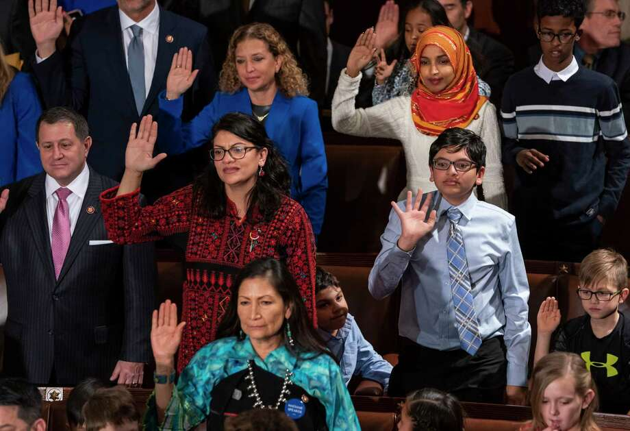 Democratic members of the House of Representatives takes their oath on the opening day of the 116th Congress as the Democrats take the majority from the GOP, at the Capitol in Washington, Thursday, Jan. 3, 2019. On the top row are, Rep. Debbie Wasserman Schultz, D-Fla., left, and Rep. Ilhan Omar, D-Minn., middle row, Rep. Joe Morelle, D-N.Y., left, and Rep. Rashida Tlaib, D-Mich., and on the bottom row, Rep. Deb Haaland, D-N.M., the first Native American woman elected to Congress. They are joined by children and family members, a tradition on the first day of the new session. (AP Photo/J. Scott Applewhite) Photo: J. Scott Applewhite / Copyright 2019 The Associated Press. All rights reserved.