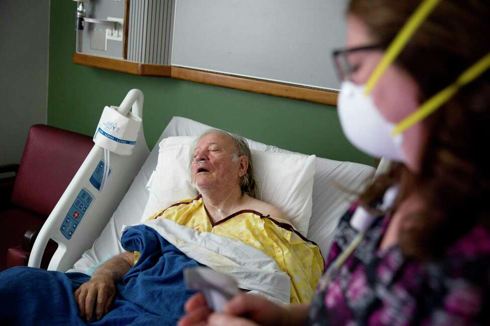 FILE - In this Friday, Feb. 9, 2018 file photo, Henry Beverly, 73, battles the flu while tended to by nurse Kathleen Burks at Upson Regional Medical Center in Thomaston, Ga. (AP Photo/David Goldman)