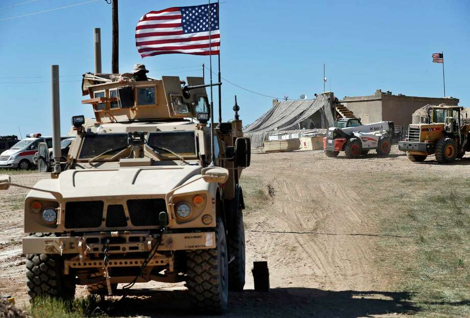 FILE - In this Wednesday, April 4, 2018 file photo, a U.S. soldier, left, sits on an armored vehicle behind a sand barrier at a newly installed position near the front line between the U.S-backed Syrian Manbij Military Council and the Turkish-backed fighters, in Manbij, north Syria. The U.S. military said Friday it has started pulling equipment, but not troops, out of Syria as a first step in meeting President Donald Trump's demand for a complete military withdrawal. (AP Photo/Hussein Malla, File) Photo: Hussein Malla / Copyright 2019 The Associated Press. All rights reserved.