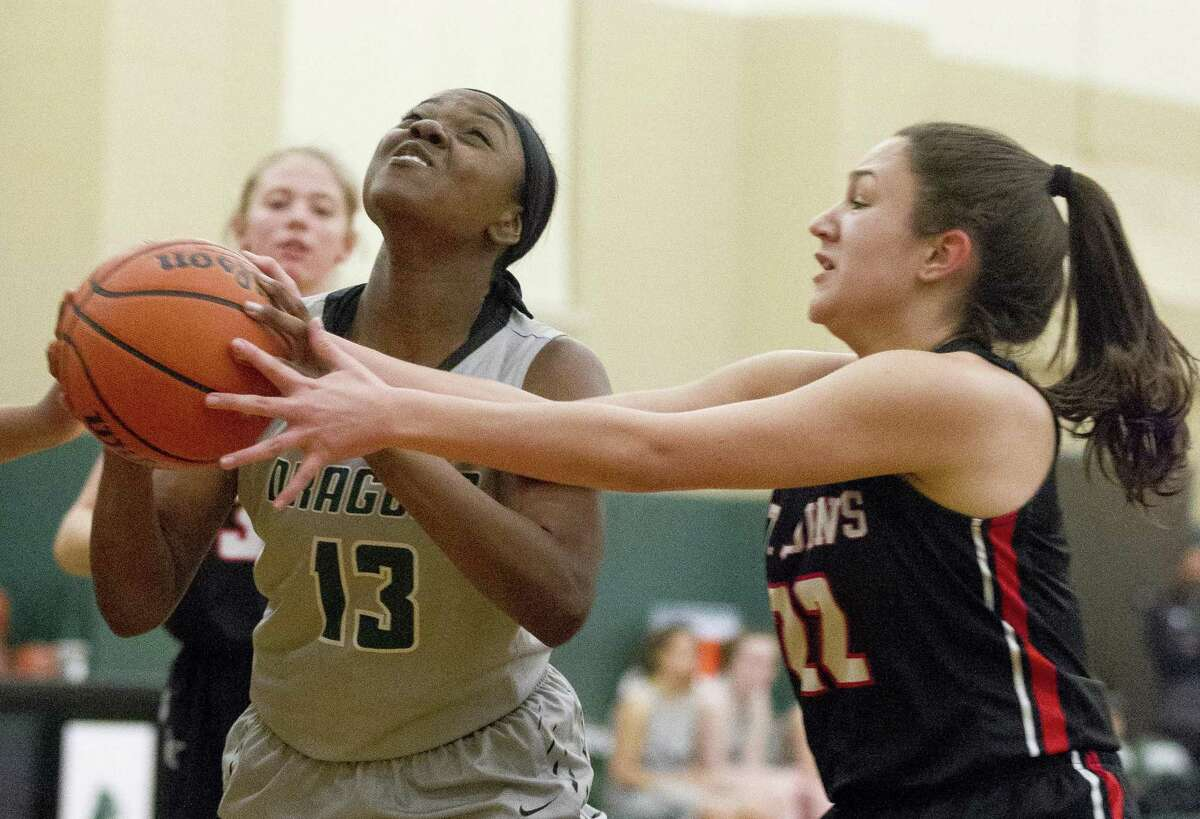John Cooper guard Ajailah Ogiemwonyi (13) is fouled by St. John guard Ana Maria Rodriguez (22) during the first quarter of a Southwest Preparatory Conference high school basketball game at The John Cooper School, Friday, Jan. 11, 2019, in The Woodlands.