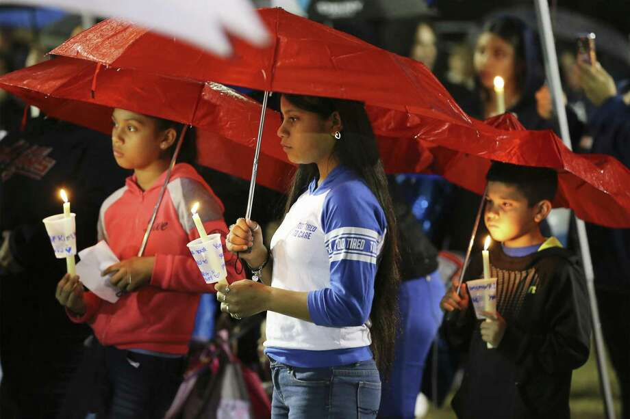 Mercedes Zamora (center) along with her sister Lexus (left) join others in attending a prayer vigil in the rain for King Jay Davila, the 8-month-old baby who has been missing for nearly a week, on Friday, Jan. 11, 2019 in Monterrey Park. On Thursday prior to tonight's vigil, law enforcement reported that the child's body was found. (Kin Man Hui/San Antonio Express-News) Photo: Kin Man Hui, Staff Photographer / San Antonio Express-News / ©2019 San Antonio Express-News