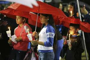 Mercedes Zamora (center) along with her sister Lexus (left) join others in attending a prayer vigil in the rain for King Jay Davila, the 8-month-old baby who has been missing for nearly a week, on Friday, Jan. 11, 2019 in Monterrey Park. On Thursday prior to tonight's vigil, law enforcement reported that the child's body was found. (Kin Man Hui/San Antonio Express-News)