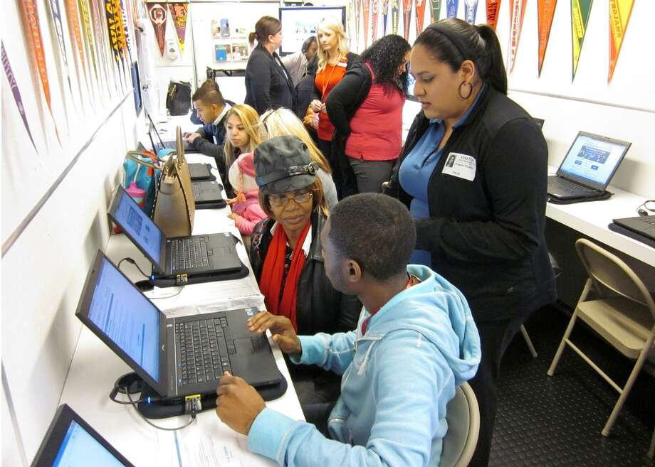 San Jacinto College recruiter Angela Flores (standing) assists PACE Center student Kevin Hunter (seated, front) and his grandmother with completing the Free Application for Federal Student Aid (FAFSA) on Feb. 5. Photo: Courtesy Pearland ISD / Courtesy Pearland ISD