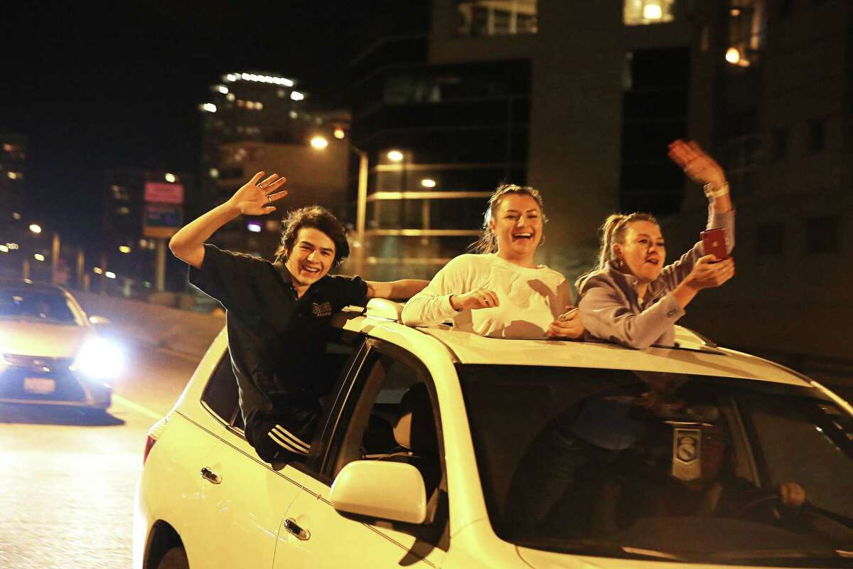 People wave fromtheir cars as others walk around on the Alaskan Way Viaduct as it is closed for the final time before its demolition, Friday, Jan. 11, 2018.