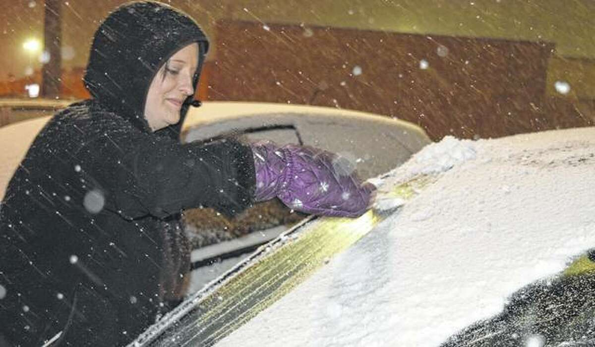 Bethany Farris of White Hall clears her car window Friday night outside Wendy's after the start of the snow storm.