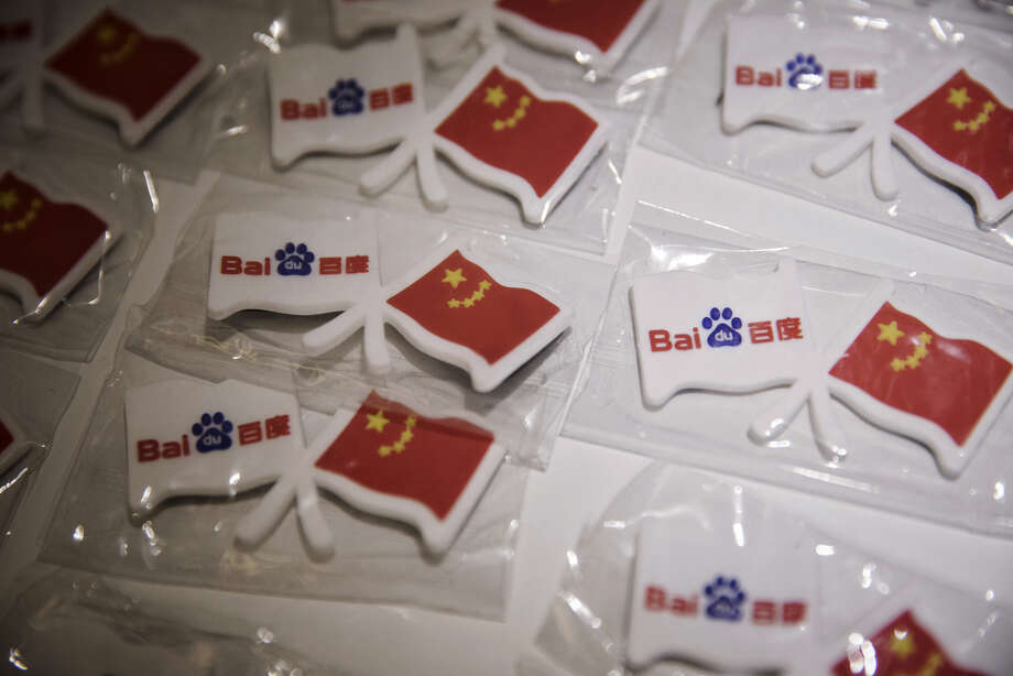 Magnets featuring the logo of Baidu Inc., left, and the Chinese national flag are displayed for sale at a coffee shop at the Baidu Technology Park in Beijing. Photo: Bloomberg Photo By Qilai Shen / Bloomberg