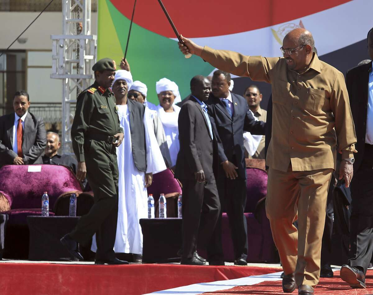 FILE - In this Wednesday, Jan. 9, 2019 file photo, Sudanese President Omar al-Bashir greets his supporters at a rally in Khartoum, Sudan. With violent anti-government protests into their fourth week, Sudan appears headed toward political paralysis, with drawn out unrest across much of the country and a fractured opposition without a clear idea of what to do if their wish to see the country's leader of 29 years go comes true. (AP Photo/Mahmoud Hjaj, file)
