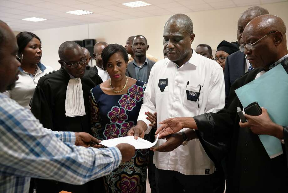 Accompanied by his wife and his lawyers, Congo opposition candidate Martin Fayulu receives the receipt after petitioning the constitutional court following his loss in the presidential elections in Kinshasa, Congo, Saturday Jan. 12, 2019. The ruling coalition of Congo's outgoing President Joseph Kabila has won a large majority of national assembly seats, the electoral commission announced Saturday, while the presidential election runner-up was poised to file a court challenge alleging fraud. (AP Photo/Jerome Delay) Photo: Jerome Delay / Associated Press