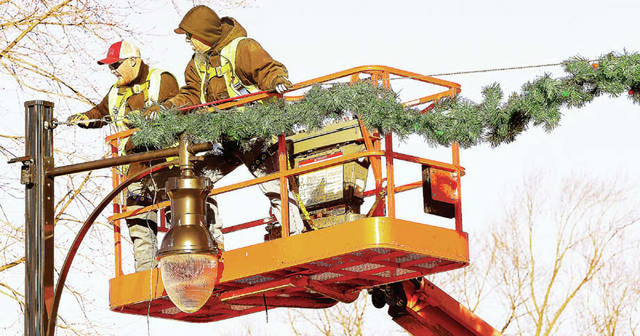 It wasn't exactly the law of gravity in force Tuesday, but Roxana Public Works Department employees were back on the lift proving that what they put up, must come back down. The crews were removing the annual Christmas decorations on Central Avenue. Photo: John Badman | The Telegraph
