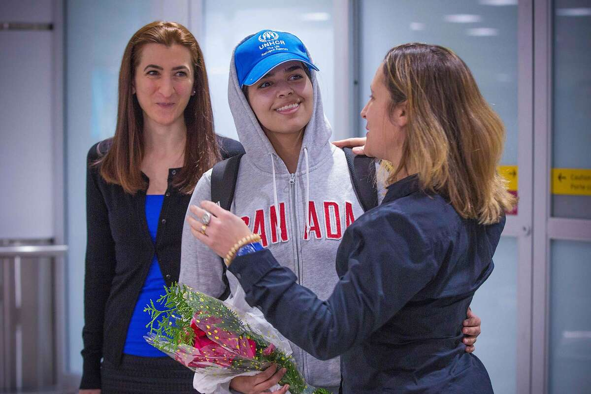 Saudi teenager Rahaf Mohammed al-Qunun (C, blue cap) is welcomed by Canadian Minister for Foreign Affairs Chrystia Freeland (R) as she arrives at Pearson International airport in Toronto, Ontario, on January 12, 2019. - The young Saudi woman who fled her family seeking asylum abroad is scheduled to land in Canada on Saturday after successfully harnessing the power of Twitter to stave off deportation from Thailand. Rahaf Mohammed al-Qunun, 18, was already en route to Toronto late Friday when Prime Minister Justin Trudeau announced that Canada would take her in. (Photo by Lars Hagberg / AFP)LARS HAGBERG/AFP/Getty Images