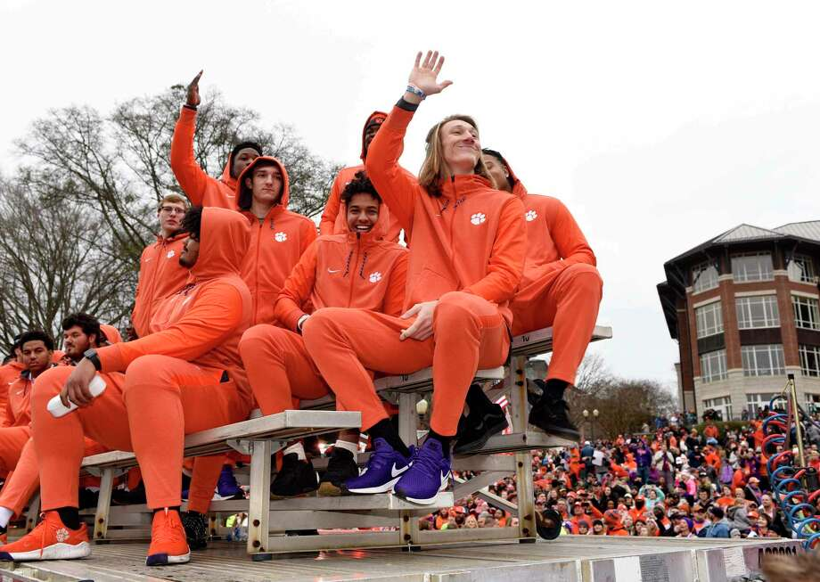 Clemson quarterback Trevor Lawrence, right, along with fellow freshman ride in the parade honoring Clemson Saturday, Jan. 12, 2019, in Clemson, S.C., Clemson defeated Alabama 44-16 in the College Football Playoff championship game Monday Jan. 7. Photo: Richard Shiro, AP / FR159523 AP