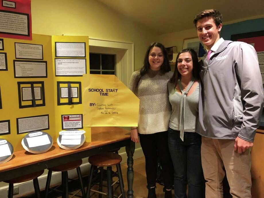 Greenwich High School seniors Courtney Swift, Sophia Fernandez and Nic de la Sierra stand next to their school start time research presentation for their senior project for Innovation Lab, the school within GHS that emphasizes interdisciplinary learning and learning through projects. The students, who comprise the second graduating class from Innovation Lab, broke down the biases behind arguments for and against the start time change by looking at student, teacher and parent surveys, and speaking with Interim Headmaster Rick Piotrzkowski. Photo: Jo Kroeker / Hearst Media Group
