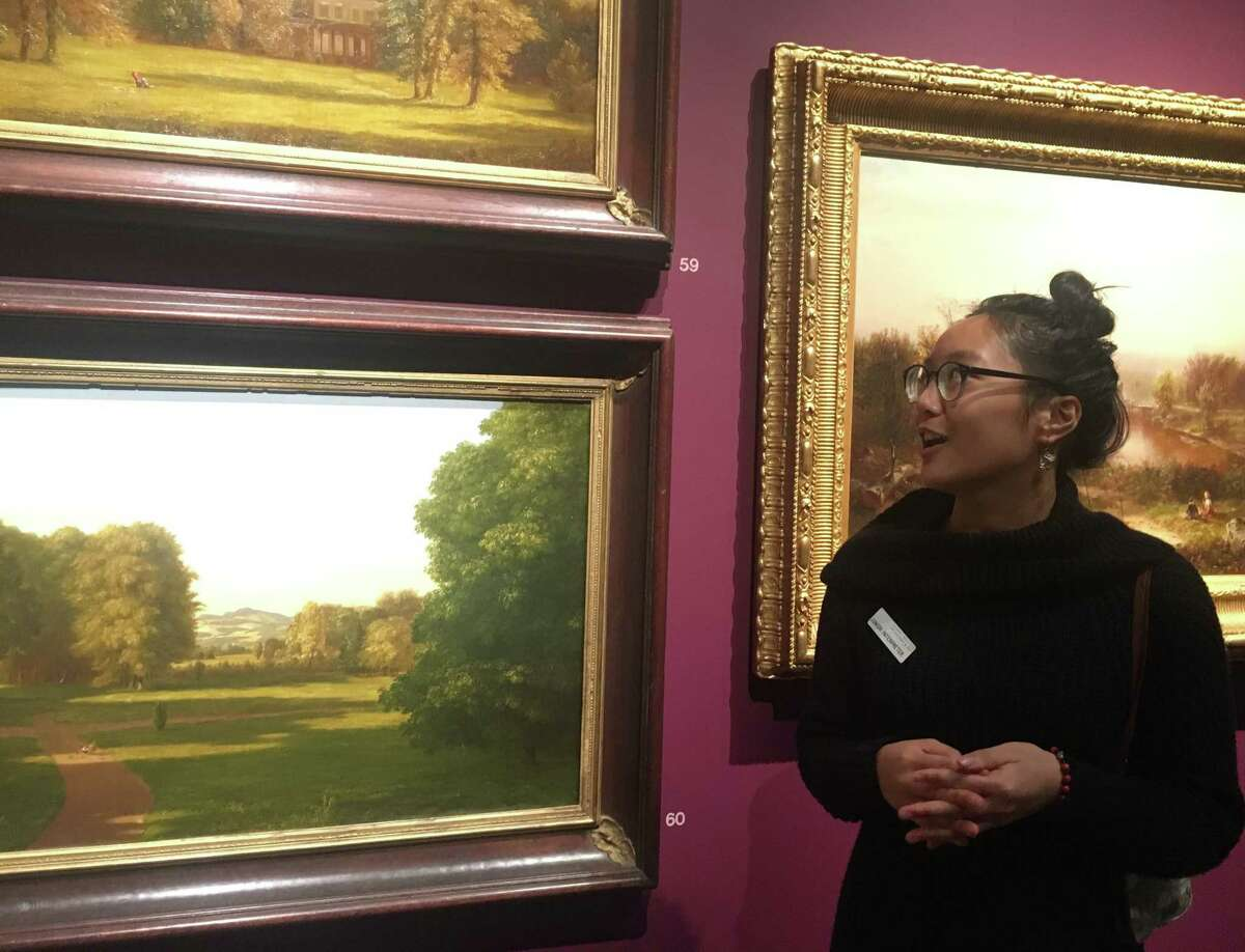 """John Ezra Malibago, a senior at Colonie Central High School, explains the historical context of a pair of Thomas Cole painting on display at the Albany Institute of History and Art as part of the museum's """"junior interpreters"""" program."""