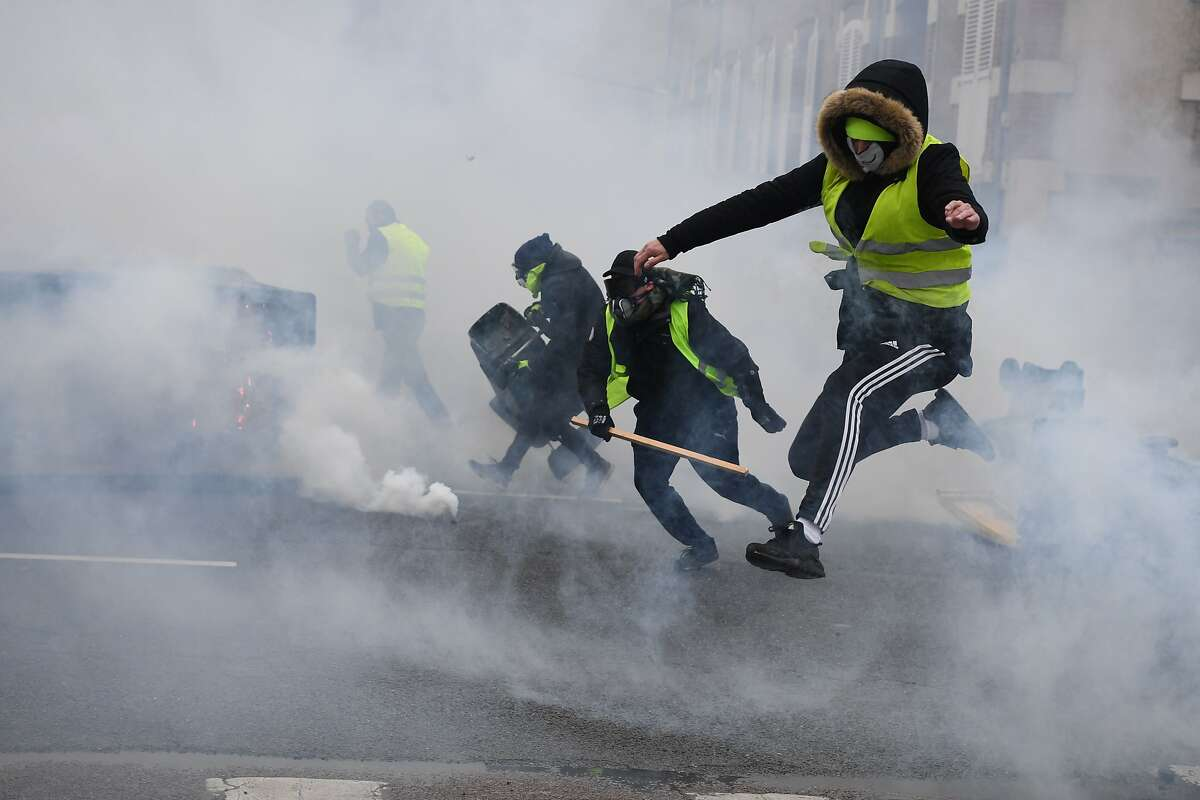 Protesters wearing Yellow Vests (Gilets Jaunes) run away from tear gas during an anti-government demonstration called by the Yellow Vests