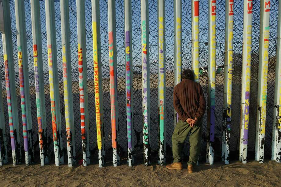 TIJUANA, MEXICO - JANUARY 06: A man looks through the U.S.-Mexico border wall in the Las Playas area on January 6, 2019 in Tijuana, Mexico.  The U.S government is going into the third week of a partial shutdown with Republicans and Democrats at odds on agreeing with President Donald Trump's demands for more money to build a wall along the U.S.-Mexico border.(Photo by Sandy Huffaker/Getty Images) Photo: Sandy Huffaker / 2019 Getty Images