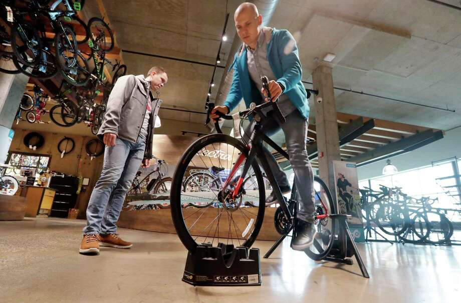 "FILE- In this Nov. 13, 2018, photo Vitalii Myroshnychenko, right, test rides a bike atop a stand as Denis Rybalchenko looks on in REI Co-op's flagship store in Seattle. The usual advice is ""buy experiences, not things."" But that requires a deeper dive. A bicycle can provide an experience, and a new camera can preserve one. So buy experiences, especially with other people, but also think about buying material things that allow you to have experiences or enhance them. (AP Photo/Elaine Thompson, File) Photo: Elaine Thompson / Copyright 2019 The Associated Press. All rights reserved."
