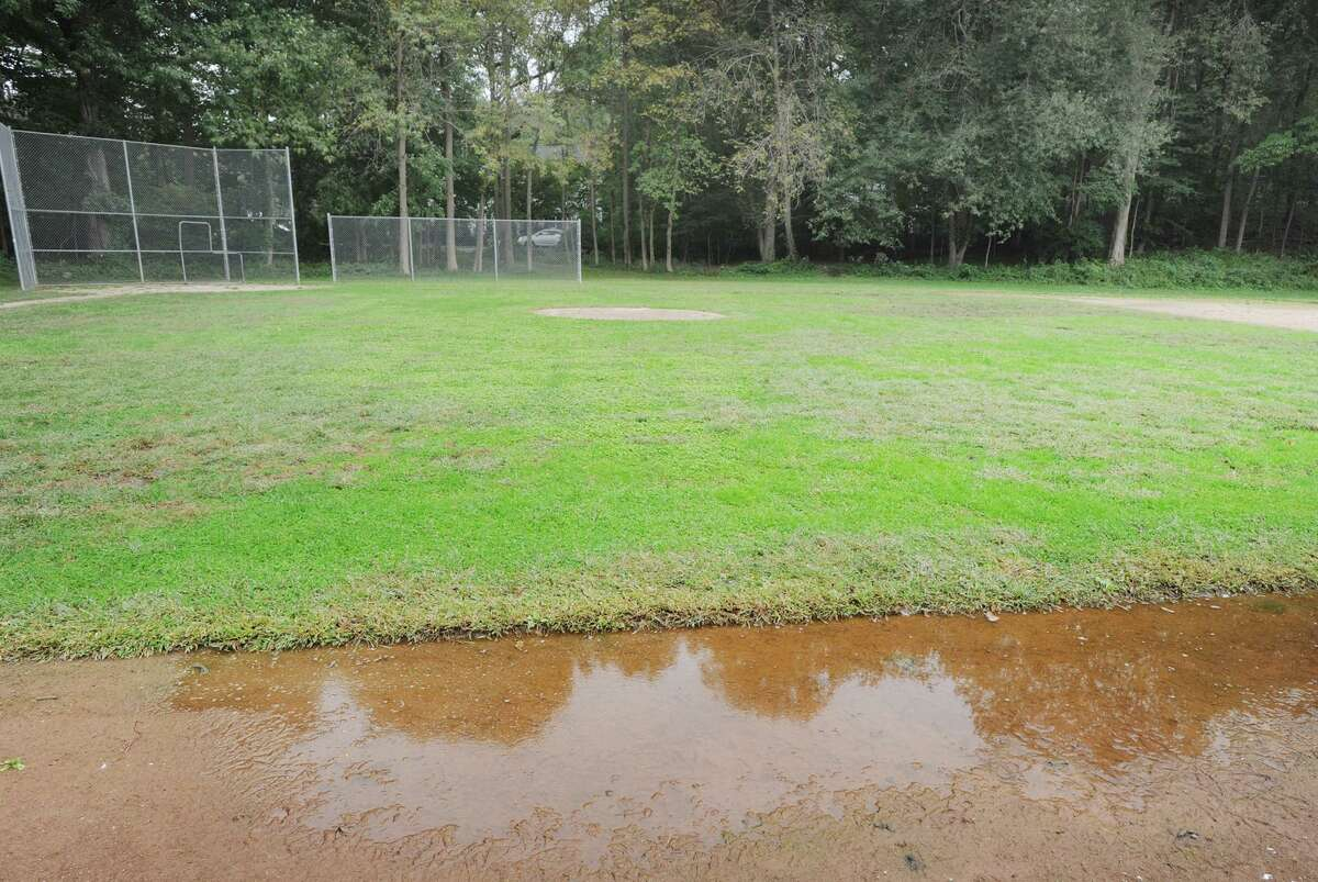 Standing water can be seen on the infield of the baseball diamond that is part of the athletic fields at Central Middle School in Greenwich, Conn., Thursday, Oct. 4, 2018.