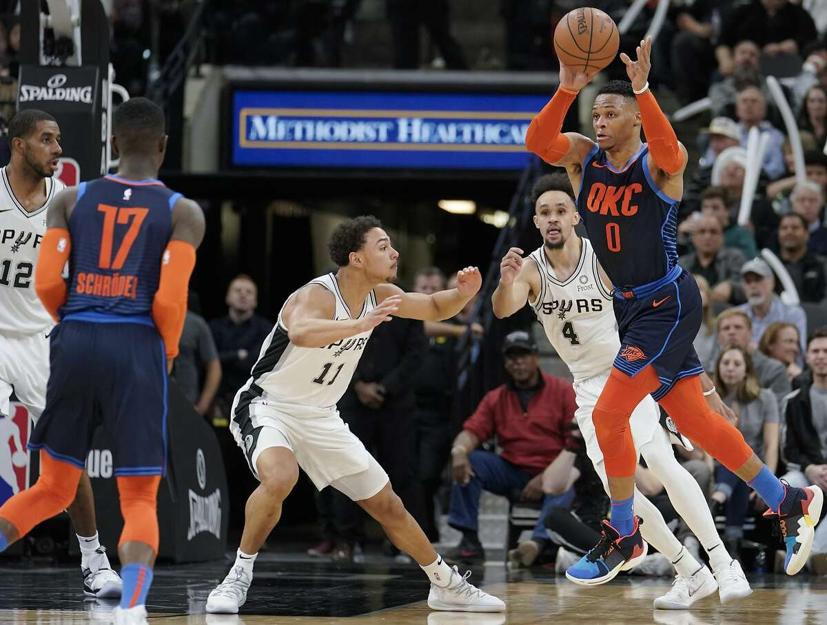 Oklahoma City Thunder's Russell Westbrook (0) passes to teammate Dennis Schroder (17) as he is defended by San Antonio Spurs' Bryn Forbes (11) and Derrick White (4) during the second half of an NBA basketball game, Thursday, Jan. 10, 2019, in San Antonio. San Antonio won 154-147 in double overtime. (AP Photo/Darren Abate)
