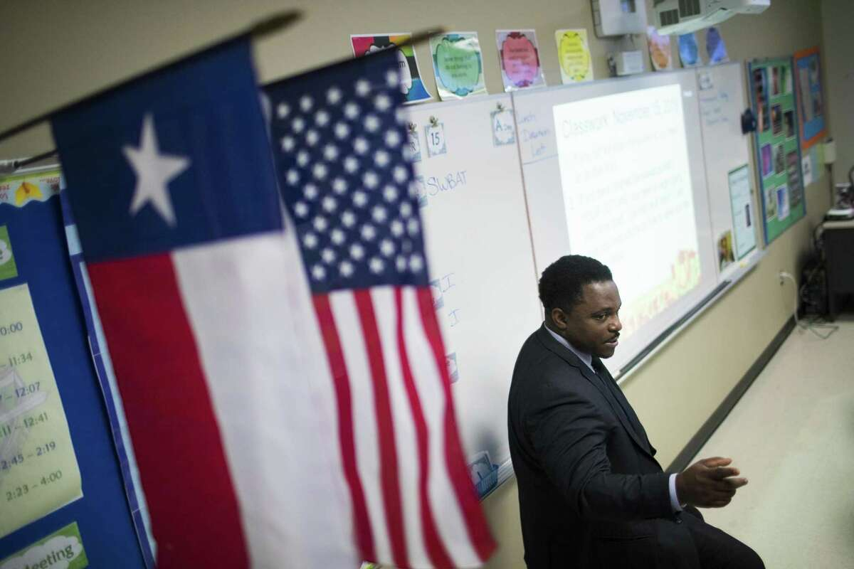 Mickey Leland College Preparatory Academy for Young Men founding principal Dameion Crook interacts with seventh graders working on an assignment about creating original ideas during class, Thursday, Nov. 15, 2018, in Houston.