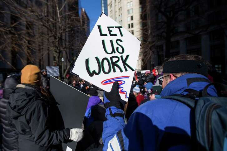 "A demonstrator holds a sign that reads ""Let Us Work"" during a protest against the government shutdown in Boston, Massachusetts, U.S., on Friday, Jan. 11, 2019. The partial government shutdown stretched into its 21st day Friday, as judges, law enforcement officers, NASA engineers, weather forecasters and office staff were among some 800,000 federal workers who missed their first paychecks. Photographer: Scott Eisen/Bloomberg"