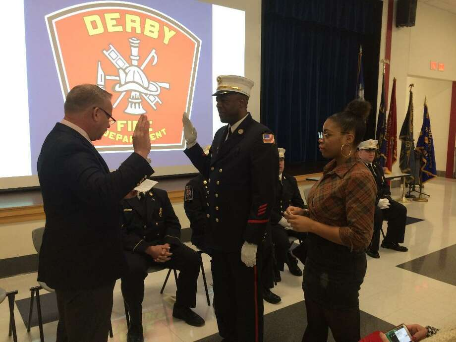 Derby Mayor Richard Dziekan administers the oath to Michael Gloade, as the city's second assistant fire chief on Saturday, Jan. 12, 2019. Gloade, a Stamford accountant, will make history as the city's first black chief in 2023. His daughter, Madeline, a student at the University of Massachusetts at Amherst watches. Photo: / Michael P. Mayko